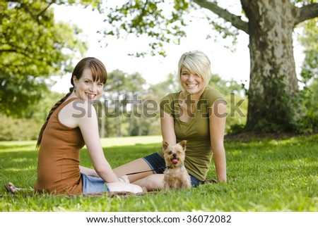 Young women sitting with dog at a park