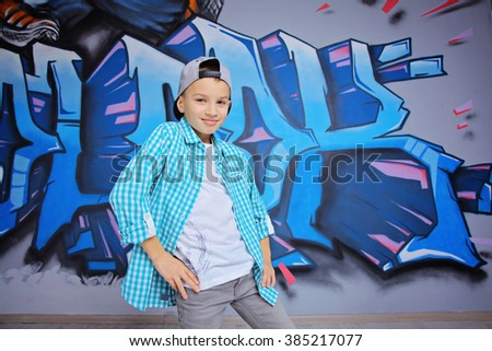 young 10-years boy posing in front of a colorful graffiti wall. Teenager boy dancing hip hop over textured background