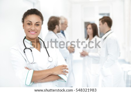 Your health guardian. Beautiful African woman doctor smiling to the camera proudly posing in front of her hospital team of colleagues copyspace success happiness occupation health medical concept
