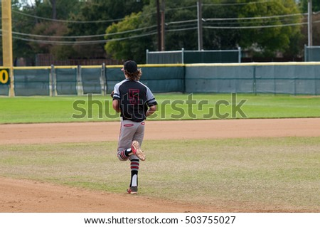 Youth baseball player running across the field during a game.