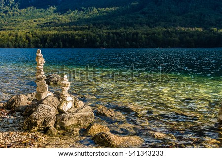 Zen, stones pyramid on shore of Bohinj Lake in Triglav National Park. Beautiful scenic view with stone pile and lake with turquoise clear water. Stones on the lake bank against a mountain landscape.