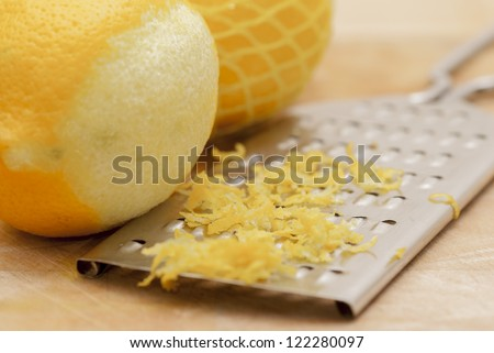 Zested lemons on wooden chopping board.