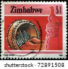 ZIMBABWE - CIRCA 1985: A stamp printed in Zimbabwe shows Playing Mbira (musical instrument) at the right Zimbabwe Bird soapstone sculpture, circa 1985 - stock photo