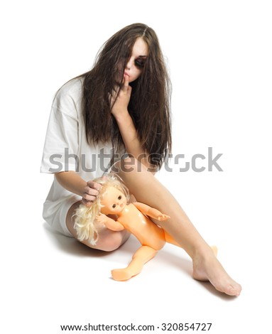 Zombie girl with plastic doll isolated
