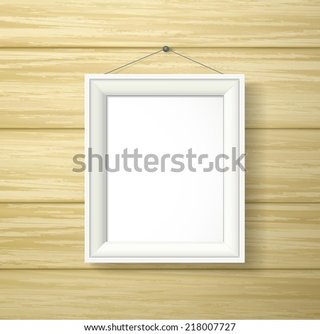 blank white photo frame hanging on the wooden wall