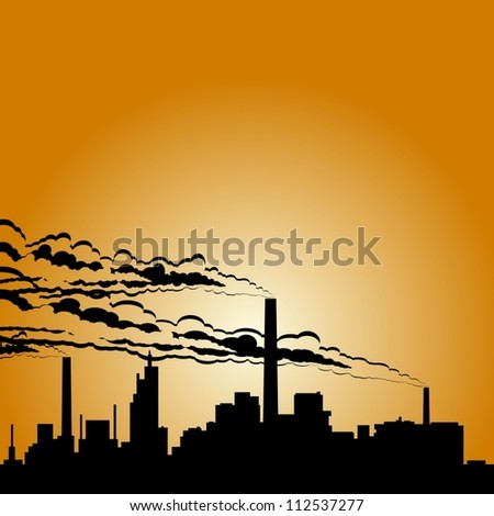 Circuit of industrial buildings and smoking chimneys against the setting sun.