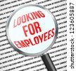 Magnifier glass over Looking for employees text in newspaper - stock photo