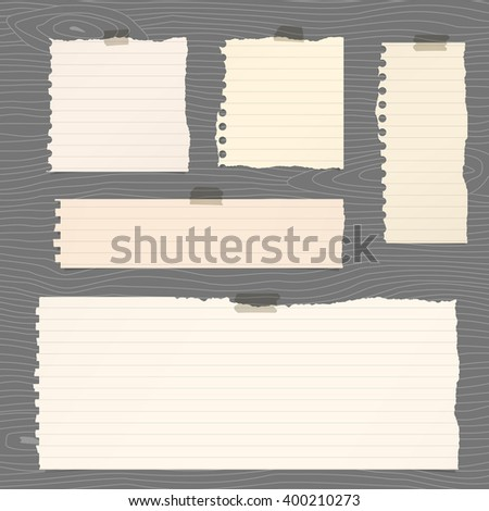 Pieces of torn brown lined note paper are stuck on gray wooden wall or board