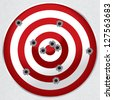 Red and white shooting range target shot full of bullet holes. - stock photo