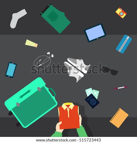 Someone packing his stuff for travel in an opened suitcase.  He puts in suitcase clothes, shoes, glasses, cosmetics,  camera and passport. Camera top view.